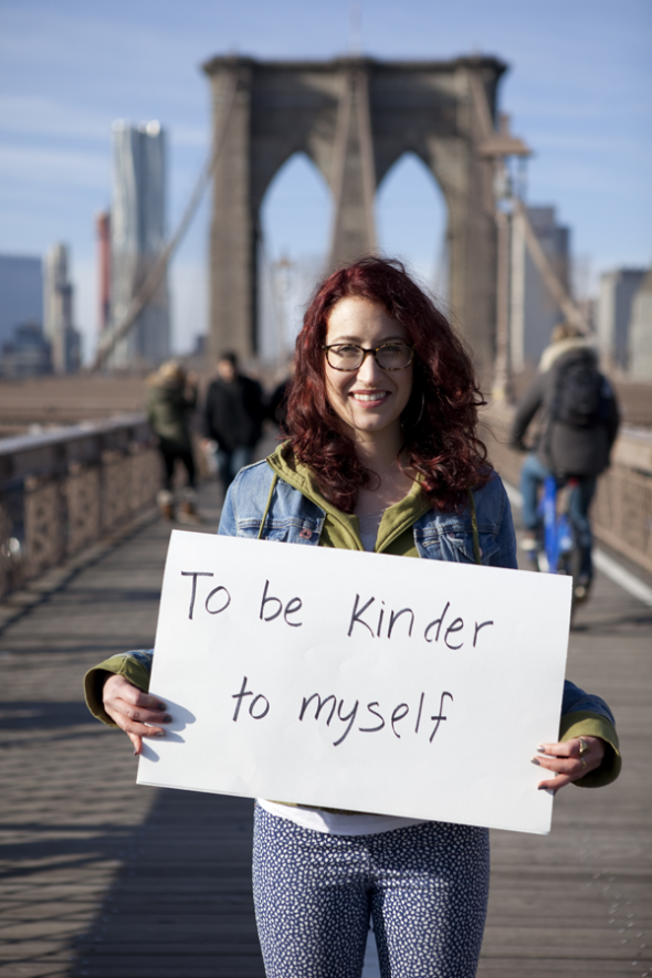 "Photo of Sabina holding a sign that says ""To Be Kinder To Myself"""